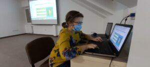 Dziewczyna siedzi przy biurku i dokonuje wpisu w prezentacji multimedialnej. To co robi, wyświetlone jest na ekranie, który znajduje się na ścianie za jej plecami.