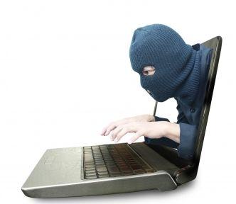 Laptop. Z ekranu wyłania się twarz w kominiarce i wyciąga ręce do klawiatury. Jest to symbol złodzieja,