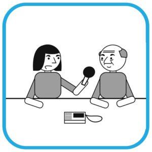Od lewej: kobieta z niepełnosprawnością intelektualną trzyma w ręce mikrofon. Do mikrofonu mówi starszy mężczyzna. Przed nimi na stole leży dyktafon.