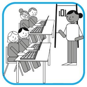 Terapeuci siedzą przed komputerami na szkoleniu. Przed nimi stoi wykładowczyni.