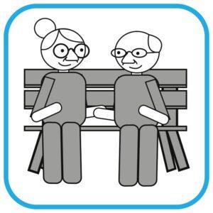 Na ławce siedzi 2 seniorów - kobieta i mężczyzna. Rozmawiają.