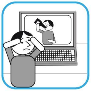 Zawstydzona osoba przed komputerem. Unosi ręce do twarzy jakby chciała zasłonić oczy. Patrzy na swoje zdjęcie na ekranie komputera. Na zdjęciu widać jak pije  alkohol z butelki.