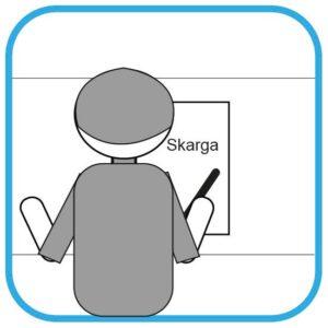 Osoba siedzi tyłem do czytelnika. Pisze pismo. Na kartce słowo Skarga.