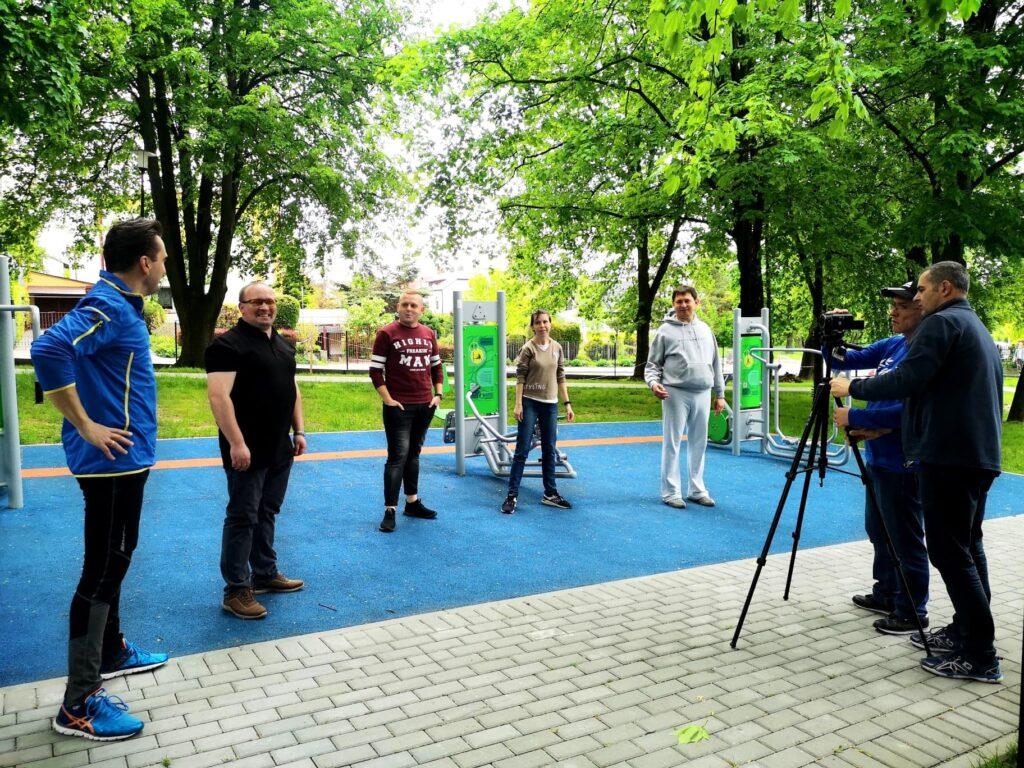 Grupa osób stoi na terenie siłowni plenerowej. Jest gotowa do nagrania filmu.