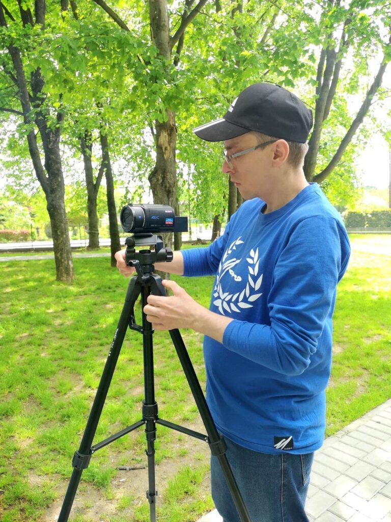 Sprawdzenie ustawień kamery. W tle znajduje się teren parku blisko siłowni plenerowej.
