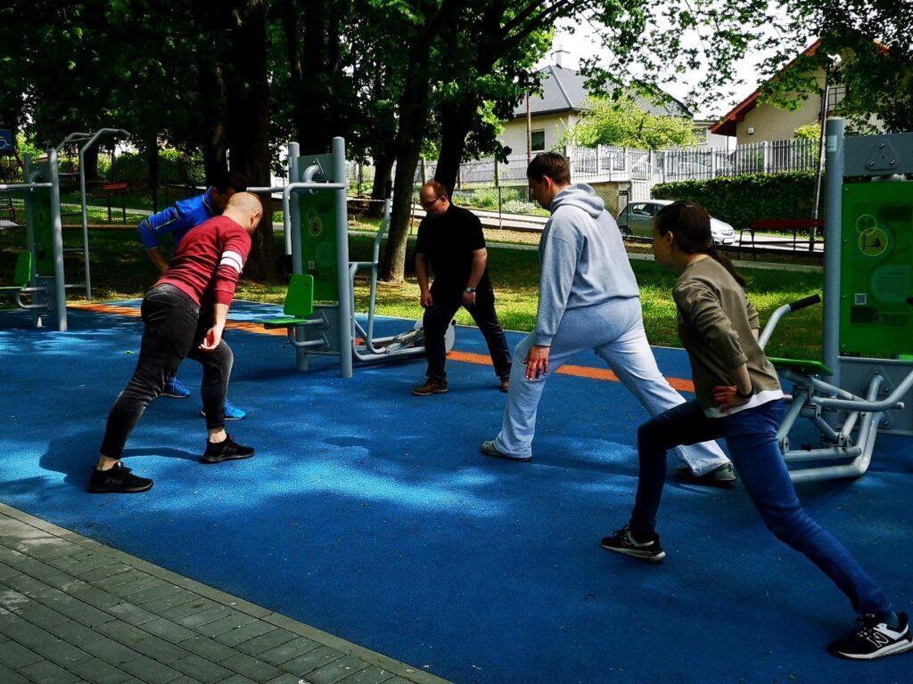 Grupa osób ćwiczy na terenie siłowni plenerowej.