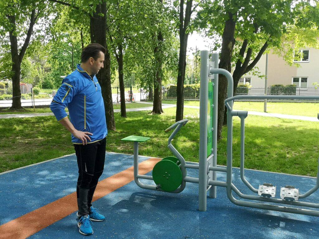 Trener patrzy na przyrządy sportowe na terenie siłowni plenerowej.