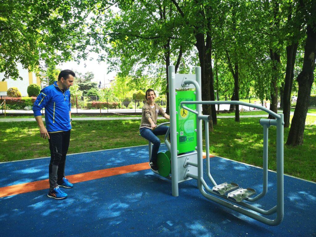 Kobieta ćwiczy pod okiem trenera na terenie siłowni plenerowej.