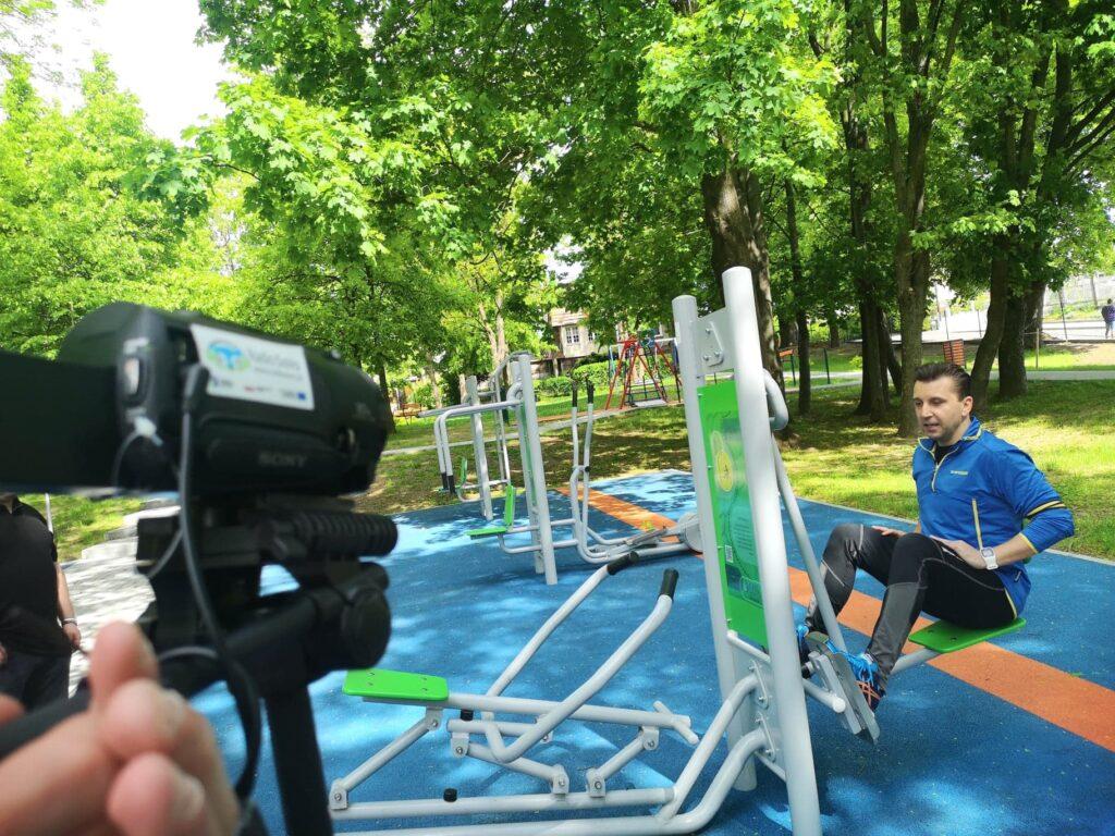 Trener ćwiczy na terenie siłowni plenerowej. W trakcie ćwiczeń jest nagrywany film.