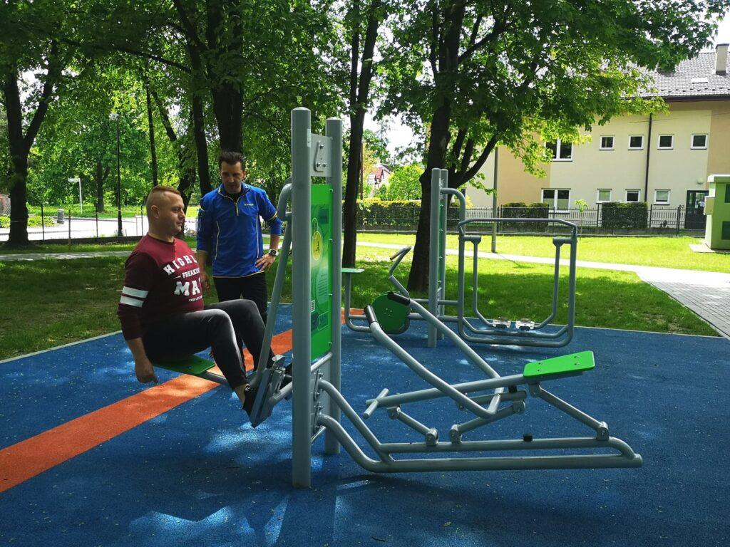 Mężczyzna ćwiczy z trenerem na terenie siłowni plenerowej.