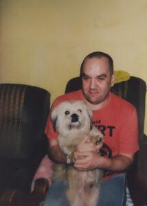 Pies siedzi na kolanach mężczyzny.