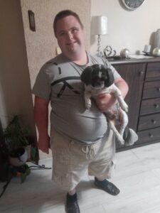 Mężczyzna nosi psa jedną ręką.