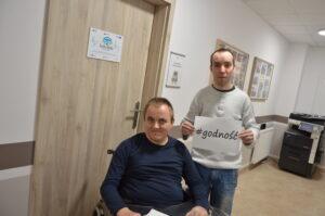 Zdjęcie dwóch mężczyzn. Jeden jest na wózku a drugi stoi obok niego i trzyma na kartce napis godność.
