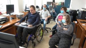 Grupa osób z niepełnosprawnościami z Radia Sovo w Biskupcu siedzi w dwóch rzędach w sali  komputerowej. Po prawej stronie 2 kobiety w maseczkach. Po lewej stronie dwóch mężczyzn.  Pierwszy mężczyzna jest na wózku. Przed nim jest mikrofon.