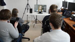 Grupa osób z niepełnosprawnościami z Radia Sovo w Biskupcu siedzi w dwóch rzędach (tyłek do  czytelnika) w sali komputerowej. Patrzą na monitor telewizora, na którym widać prezeskę PSONI.