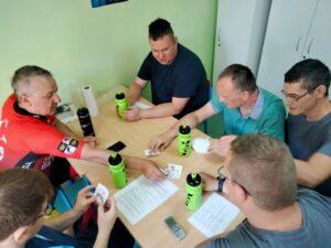 Grupa osób siedzi przy stole i rozmawia.