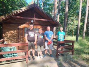 Grupa czterech mężczyzn stoi przed domkiem w lesie.
