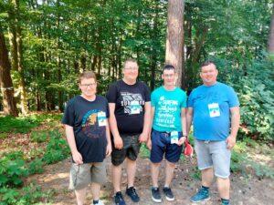 Grupa czterech mężczyzn jest w lesie.