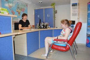 Osoba z niepełnosprawnością siedzi na krześle. Rozmawia z kobietą z biura podróży.