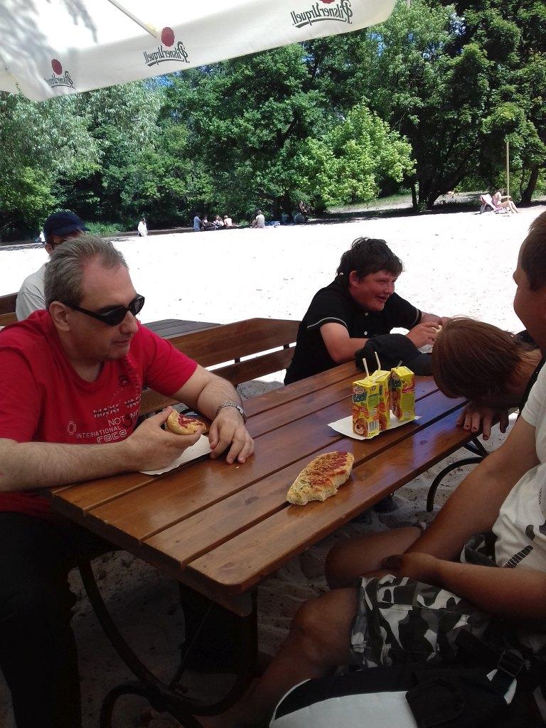 Osoby jedzą posiłek przy stole, który znajduje się na plaży.