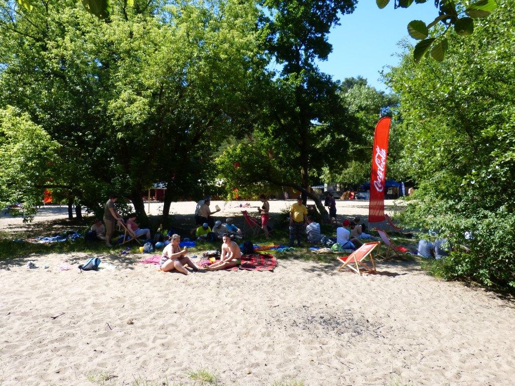 Na plaży opalają się ludzie.