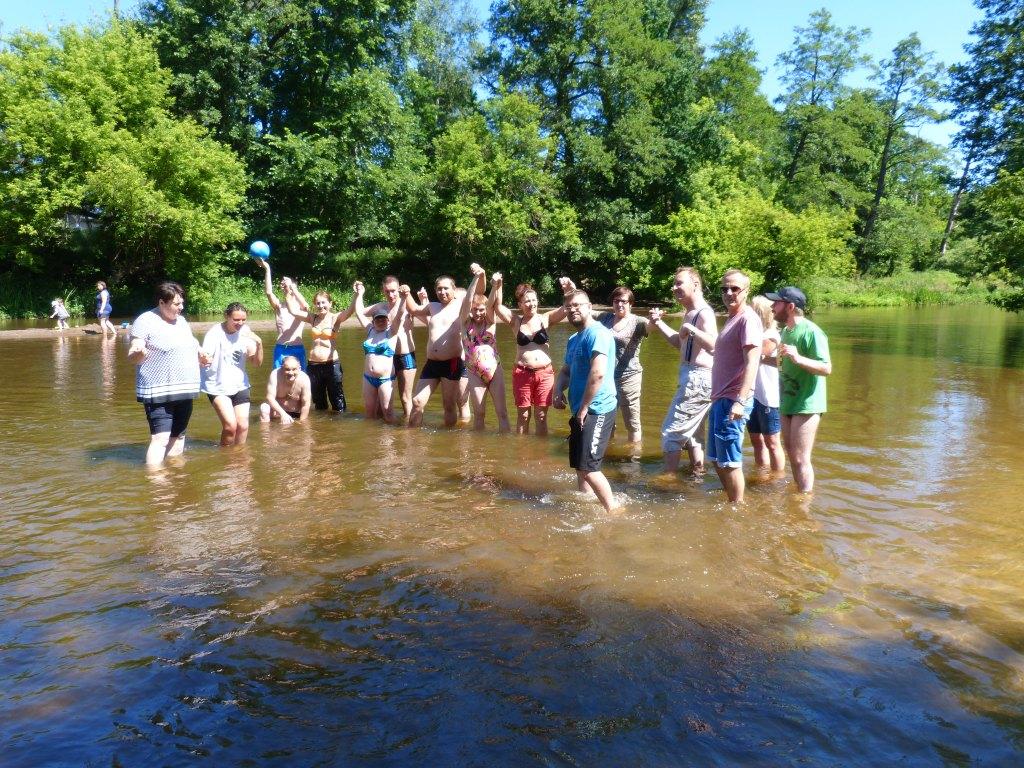 Grupa osób stoi w jeziorze. Niektórzy trzymają się za ręce.