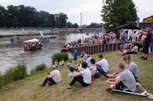 Ludzie oglądają z brzegu łodzie na rzece.